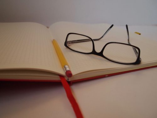 Glasses on open notebook with pencil